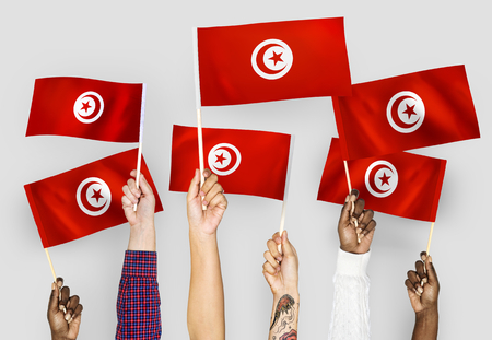 Hands waving the flags of Tunisia