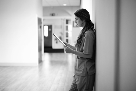Nurse reading through medical records in the hallway