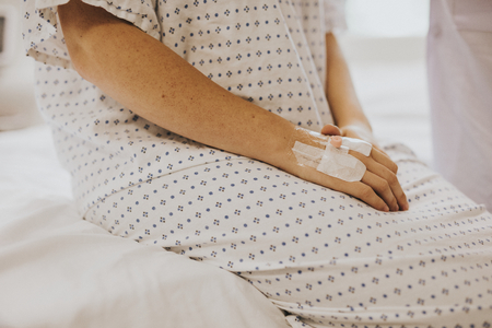 Woman sitting on her hospital bed Stock Photo