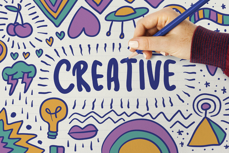 Woman drawing the word creative typography on a board Фото со стока