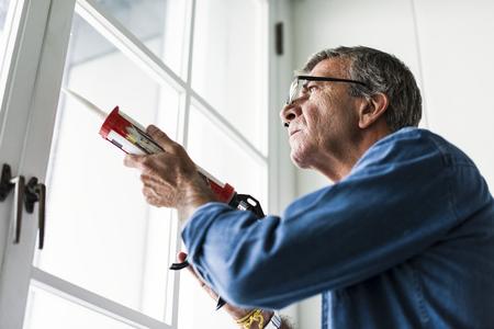 Man using a silicone gun to repair a window