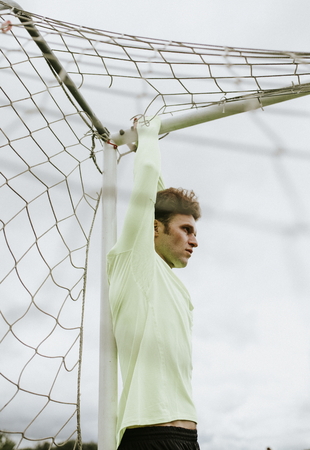 Male football goalkeeper stretching on a crossbar Stockfoto