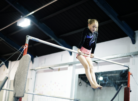 Young gymnast on a horizontal bar 免版税图像