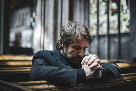 Lonely Christian man praying in the church