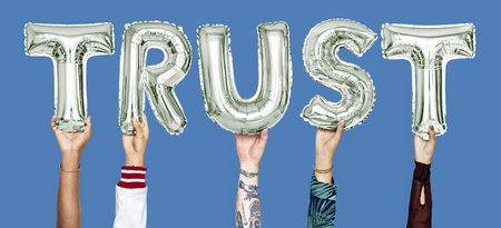 Hands holding trust word in balloon letters