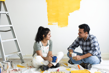 Couple taking a break from painting the walls Stock Photo