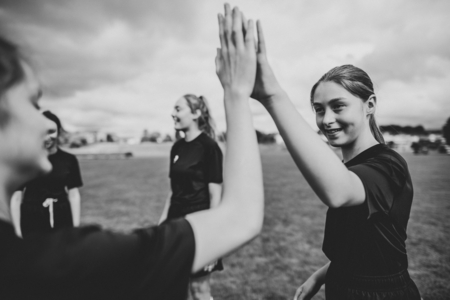 Female football players giving each other high five
