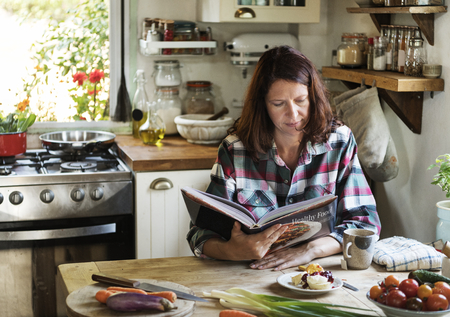 Woman reading a cookbook in the kitchen