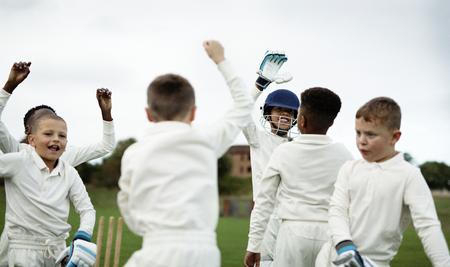 Junge glückliche Kricketspieler jubeln auf dem Feld