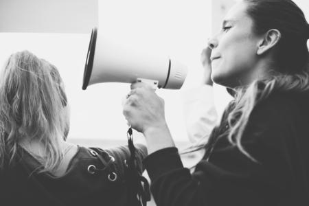 Attivista femminile che grida su un megafono Archivio Fotografico