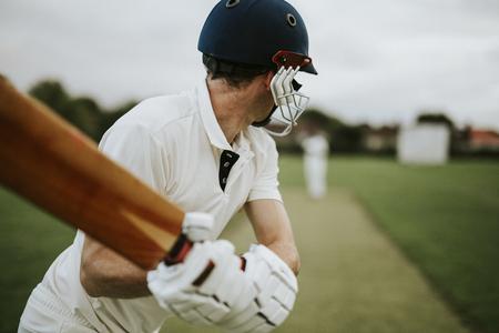 Jugador de críquet en el campo en acción Foto de archivo