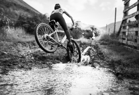 Female cyclist in action over a puddle