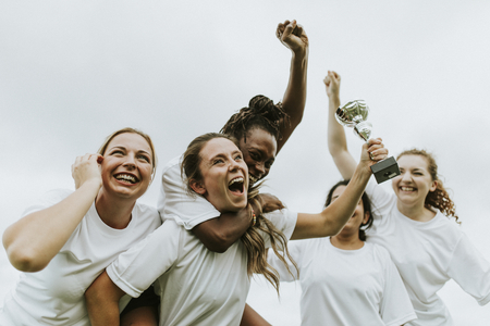 Female football players celebrating their victory Imagens