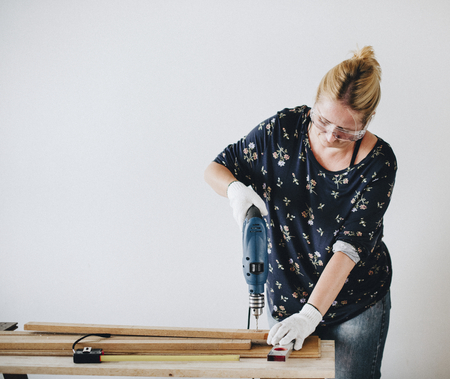 Woman drilling into a wooden plank Standard-Bild - 111926418