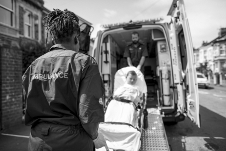 Paramedics moving a young patient on a stretcher into an ambulance
