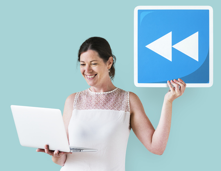 Woman holding a rewind button and a laptop Stock Photo - 111922226
