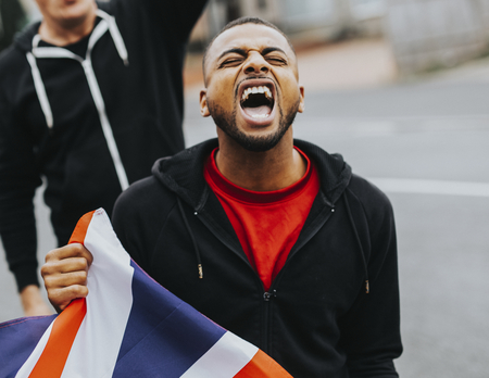 Patriot man holding a UK flag and screaming during a protest