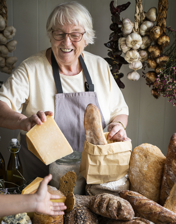 Mature woman selling cheese at a deli