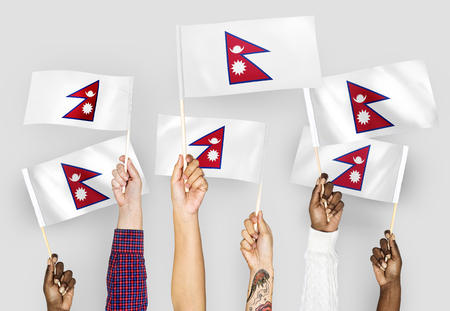 Hands waving flags of Nepal