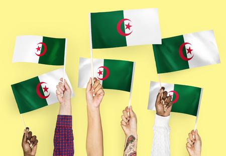 Hands waving flags of Algeria 스톡 콘텐츠 - 112145901