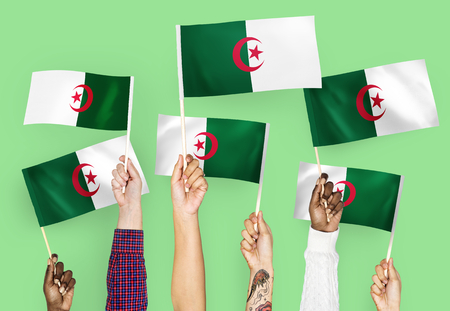 Hands waving flags of Algeria Banque d'images - 112145932