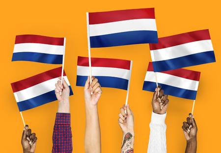 Handen zwaaien vlaggen van Nederland Stockfoto