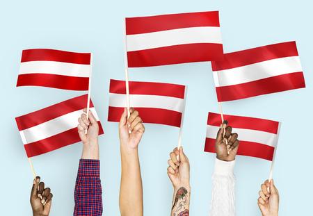 Hands waving flags of Austria