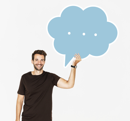 Cheerful man holding a blank speech bubble symbol
