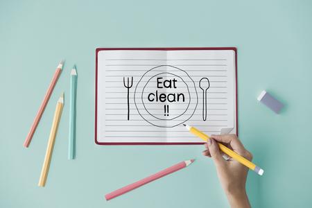 Hand writing Eat clean on a notebook