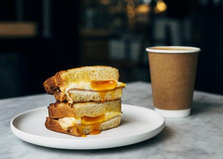 Broodje en een kopje koffie op een tafel