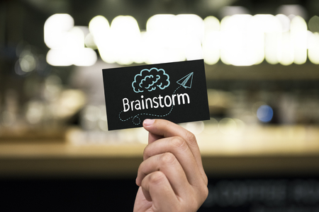 Hand holding a black paper card with a text Brainstorm