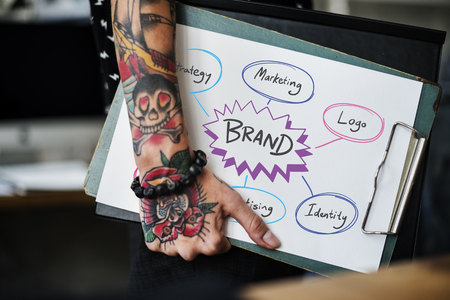 Tattooed hand holding a brand strategy clipboard Stock Photo