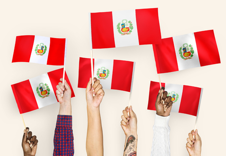 Hands waving the flags of Peru 版權商用圖片 - 112173183