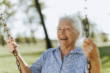Mujer mayor alegre en un columpio en un patio de recreo