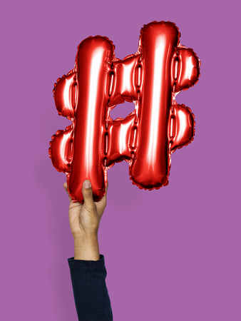Hand holding balloon hashtag symbol # Stock Photo