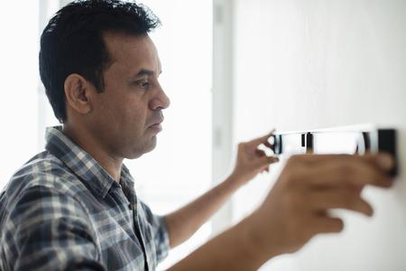 Man using a spirit level on a wall