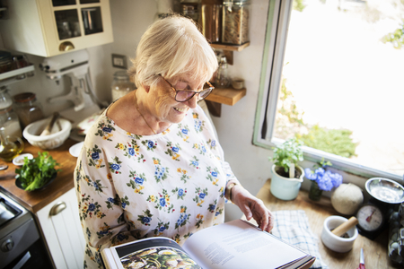 Happy elderly woman reading a cookbook Stock Photo