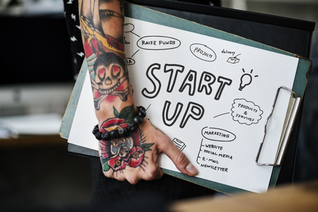 Tattooed hand holding a startup clipboard Stock Photo