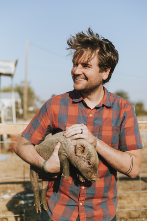 Happy young man with a piglet Stock Photo