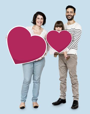 Famiglia felice che tiene le icone del cuore Archivio Fotografico