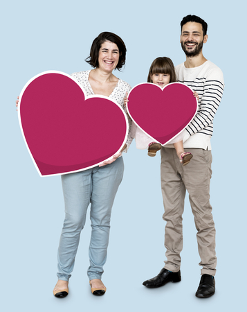 Happy family holding heart icons