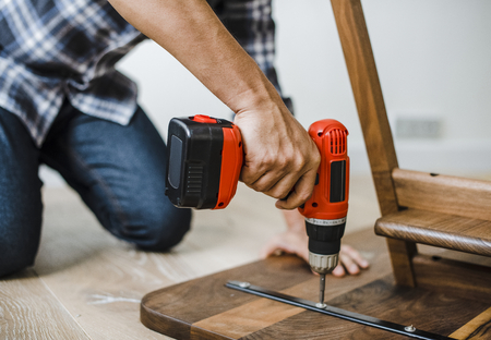 Man using hand drill to assemble a wooden table 写真素材 - 112593472