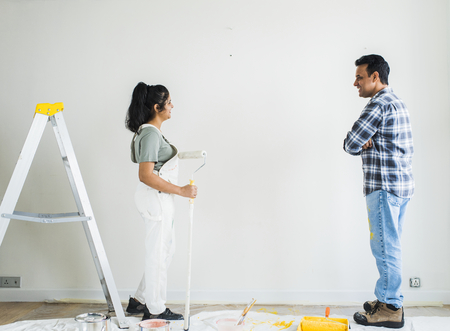 Couple painting the walls in their new apartment