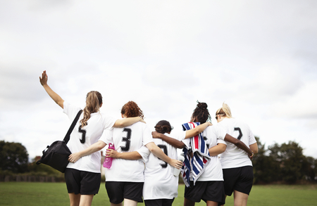 Female football players huddling and walking together Banco de Imagens