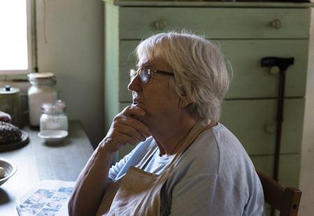 Senior woman sitting alone in her kitchen