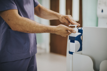 Male nurse disinfecting his hands