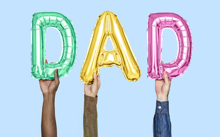 Hands holding dad word in balloon letters
