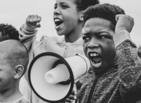 Junge, der in einem Protest auf einem Megaphon schreit
