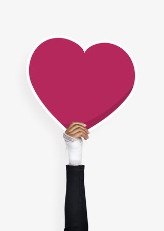 Hand holding a heart cardboard prop 스톡 콘텐츠