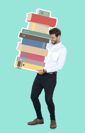 Young man carrying a stack of books Imagens